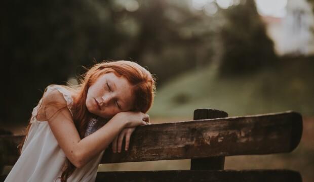 Barn sover på bænk