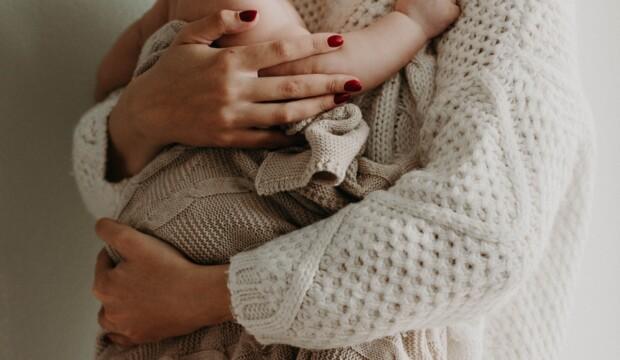 Nyfødt baby bliver holdt af sin mor