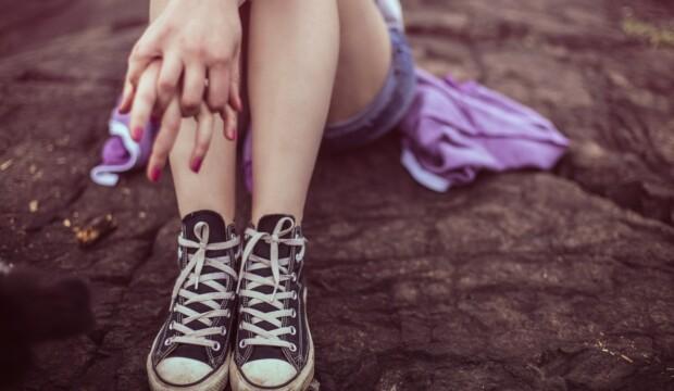 Pige sidder på sten med converse på